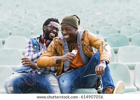 Two black race friends having fun with mobile. Friends Concept