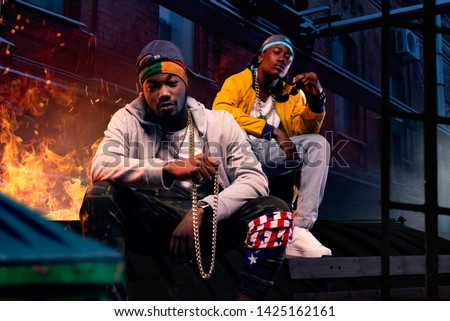 Two black rappers in caps sitting by the fire ストックフォト ©