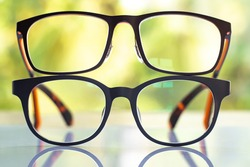 Two black shortsighted or nearsighted eyeglasses on white acrylic table, Bokeh green garden background, Close up & Macro shot, Selective focus, Reflection, Optical concept