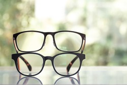 Two black shortsighted or nearsighted eyeglasses on white acrylic table, Bokeh green garden background, Close up & Macro shot, Selective focus, About Optical concept