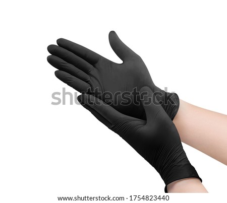 Two black surgical medical gloves isolated on white background with hands. Rubber glove manufacturing, human hand is wearing a latex glove. Doctor or nurse putting on nitrile protective gloves