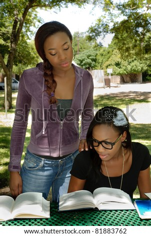 Two black teen study their books at the park, the older girl is helping the younger girl