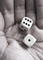 Two black white dices in hand of men ready to throw. Close lookup