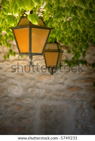 Two black wrought-iron lanterns with orange glass, hanging from a vine-covered ceiling against a stone wall. Taken in an ancient cemetery in France.