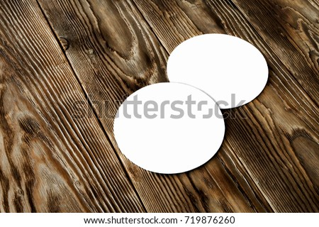 Two blank beer coasters on wooden rustic table background. Blank for new design, mock up