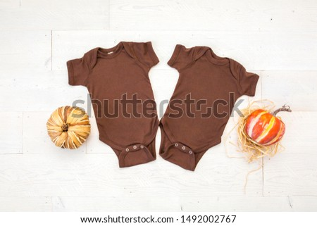 Two blank brown twin baby bodysuits, front side showing, on wood white background with two pumpkins, thanksgiving/fall mockup #1492002767