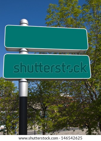 Two blank green destination signs located in an urban area