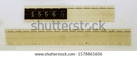 Photo of  two blank long 16mm filmstrips or snips on white fixed by transparent sticky tape
