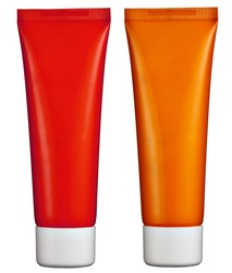 Two blank plastic cosmetics tubes, one red and one orange, isolated on white for the packaging of toiletries, makeup and beauty products