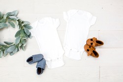 Two blank white baby bodysuits on white wood background with baby shoes and green wreath, newborn twin bodysuit mockup