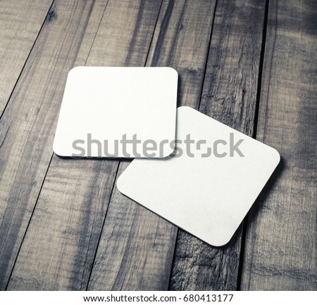 Two blank white square beer coasters on wood table background.