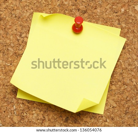 Two blank yellow sticky notes pinned onto cork board.