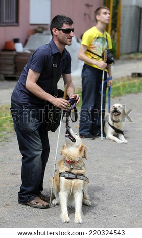 Two blind people with their guide dogs/Sofia, Bulgaria - June 25, 2014: Two blind people are giving commands to their guide dogs as part of dog\'s training.
