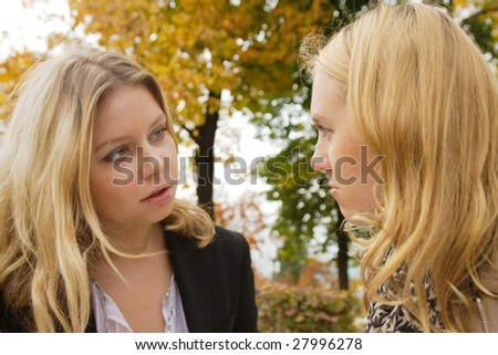 Two blond girls having serious conversation outdoors