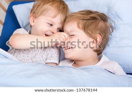 Two blond siblings having fun in bed before sleeping