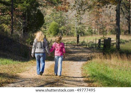 Two blond sisters holding hands and walking down an old country road in autumn