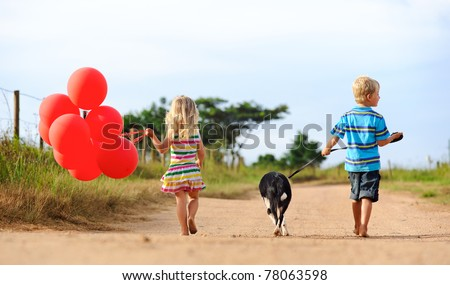 Two blonde children walking along a sandy path with red helium balloons and their puppy