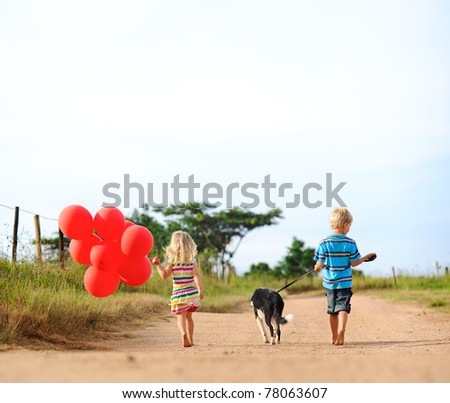 Two blonde children walking along a sandy path with red helium balloons and their puppy towards an adventure