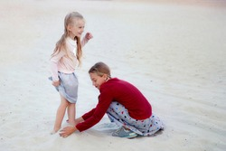 two blonde girls play on the beach on a Sunny summer day. the older sister buries the younger's feet in the sand. the younger sister laughs