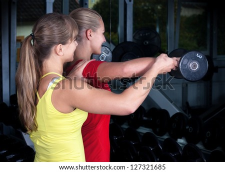 Two Blonde Women . Personal Trainer in a Gym . Two Women make sport
