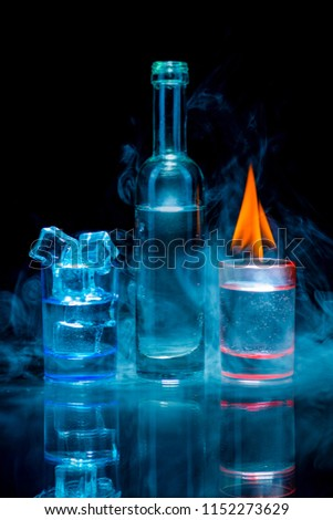 Two, blue and red shot glasses full of drinks one of wich with ice and second is burning, and a bottle in a smoke on a black background. Conceptual, commercial and advertising photo. Copy space. #1152273629