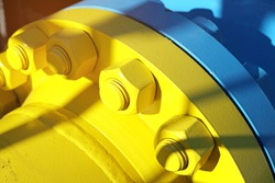 Two blue and yellow gas pipes are connected by large bolts and nuts. Background for suppliers of gas products and pipes. Close-up