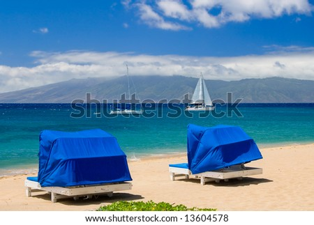 Two blue cabanas by an azure sea, sailboat and island in background