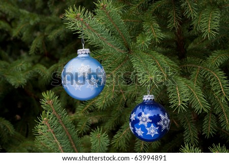two blue christmas ornaments hanging on christmas tree, both are different shades of blue
