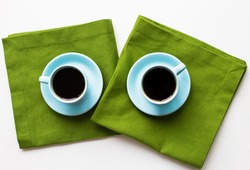 two blue cups of coffee on a table with green cloth