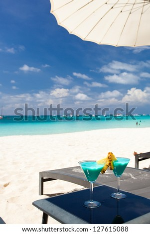two Blue Curacao cocktails with slice of pineapple on white beach