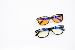 Two blue light blocking glasses (yellow and orange lenses) isolated on white background