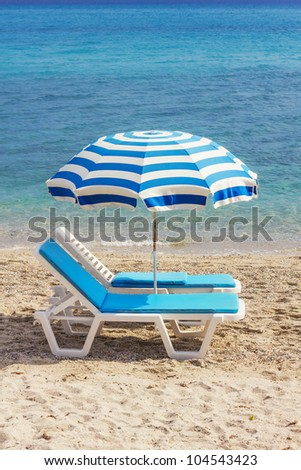 Two blue lounge chairs on a beach in Hanioti, Greece