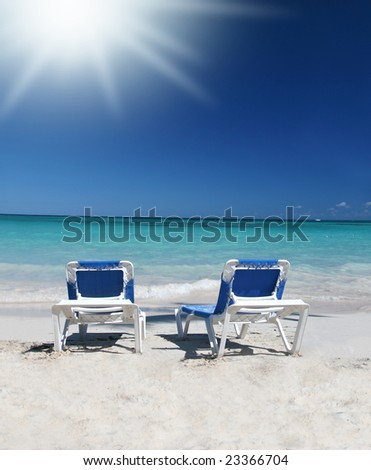 Two blue lounge chairs or beds on a beautiful Caribbean tropical beach with white sand and green ocean, suitable background for a variety of designs