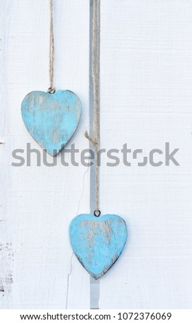 Two blue shabby chic wooden hearts hanging by string on a white vintage crate. a simple composition for valentines or a rustic wedding  #1072376069