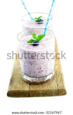 Two blueberry smoothies on an old piece of wood and shot on a white background.  Smoothies are garnished with a fresh blueberry and mint leaves.
