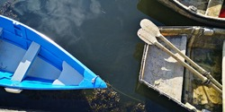 two boats, one with paddles, quite abstract poetic image