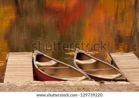 Two boats or canoes sitting in a lake during the peak of autumn in the North Carolina mountains.