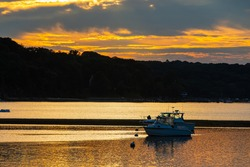 Two boats sit anchored in Cold Spring Harbor while the setting sun makes the water reflect the cloudy sky's golden yellow hues.