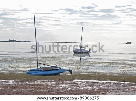 Two boats stranded in shallow water on an overcast day. Crystal Beach, Florida.