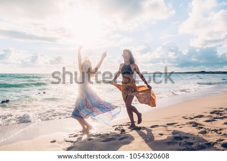 Two boho friends (girls) wearing floral maxi dress and skirt dancing on the sea shore. Bohemian clothing style. #1054320608