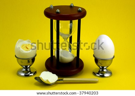 Two boiled eggs in cups with an egg timer