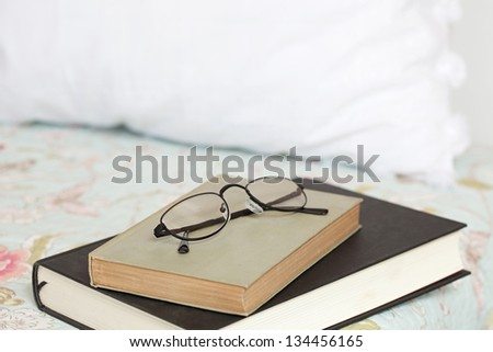 Two books and a pair of glasses laying on top of a bed in a home bedroom.