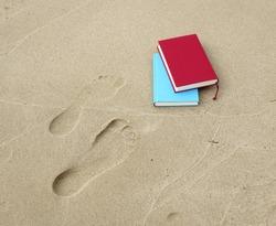 Two books lying beside two footprints.