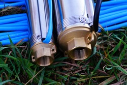 Two borehole pumps with blue and black cables lie on the grass. Submersible well pumps close-up. Inlet thread of borehole pumps.