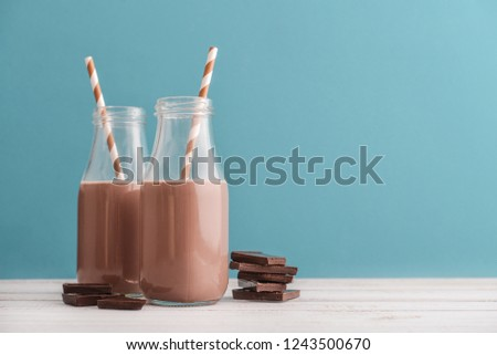 Two bottles chocolate milk with drinking straws on blue background