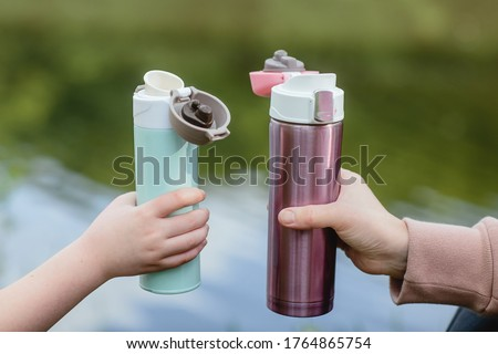 Two bottles for coffee or tea to go in hand. Concept of outdoor recreation using reusable dishes. Foto stock ©