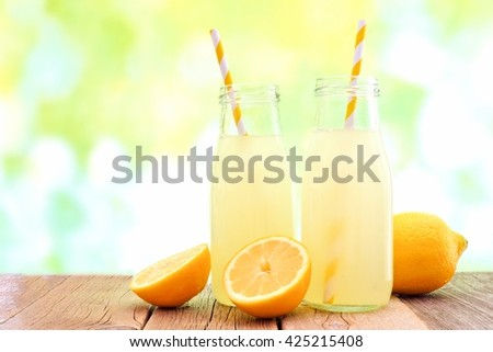 Two bottles of cold lemonade with lemon slices and straws with de-focused outdoor background