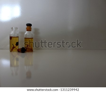 Two bottles of natural perfume, one open, containing plants, on white background #1311239942