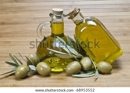Two bottles of olive oil and some green olives.