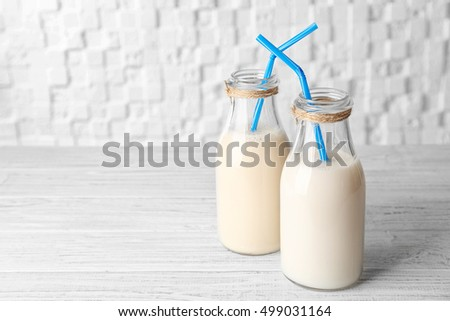 Two bottles of tasty milk with straws on wooden table against white blurred background #499031164